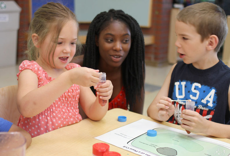 Two young kids and their caregiver with test tubes activity learning about plants and science.