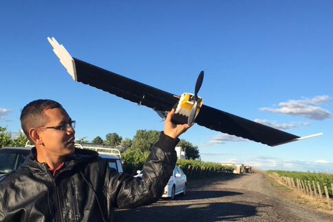 Manoj Karkee, precision agriculture researcher at Washington State University, holds a flying drone designed to deter pest birds from blueberry and wine grape plots.