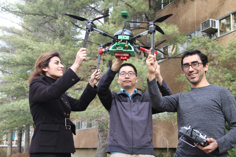 Sanaz Jarolmasjed, Chongyuan Zhang and Carlos Zuniga, WSU Biological Systems Engineering graduate students, hold a drone used in phenomics. WSU precision-ag practices help scientists use sensors and drones to understand variability in their crops. Photo by Seth Truscott-WSU CAHNRS.