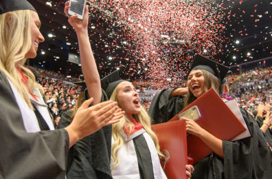 WSU graduates celebrate as confetti falls.