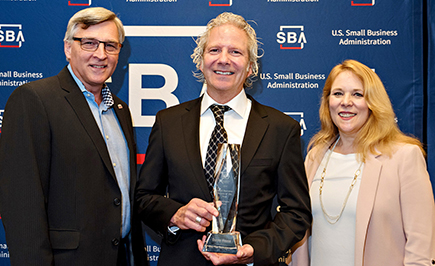 Danny House, owner of Dan the Sausageman gift baskets in Burien (center), receives SBA 2018 Small Business Person of the Year award. Rich Shockley and Jennifer Dye on on left and right, respectively, are SBDC business advisors at Highline College.