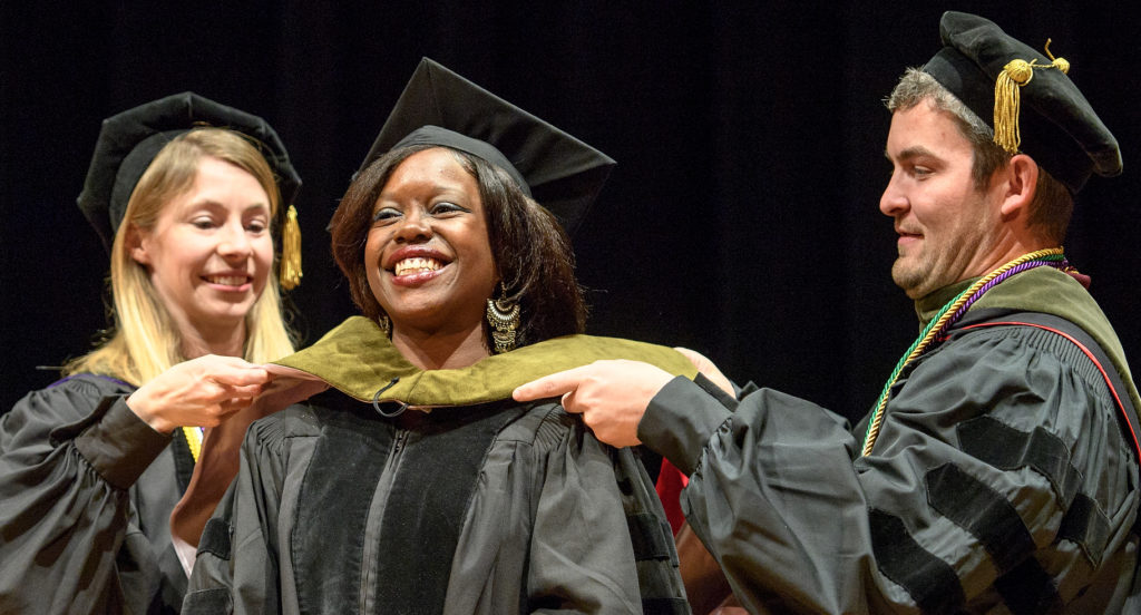 A graduate student receives her doctoral hood.