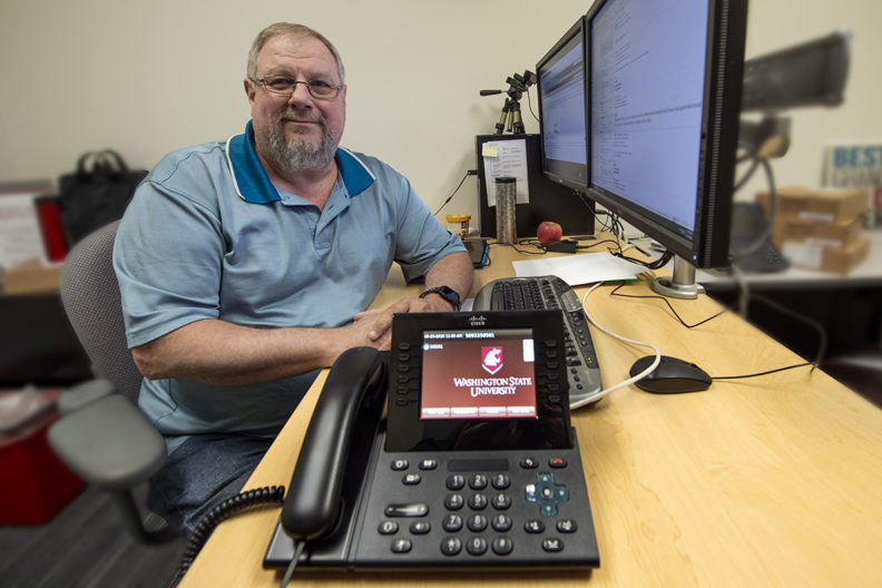 Randy Cross sits at desk, showcasing a phone with a WSU logo on its display screen.