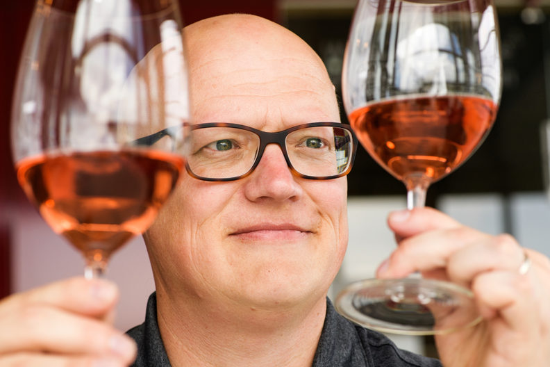 Jim Harbertson inspects two glasses of rosé wine.