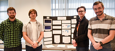 Four research team members in front of poster board.