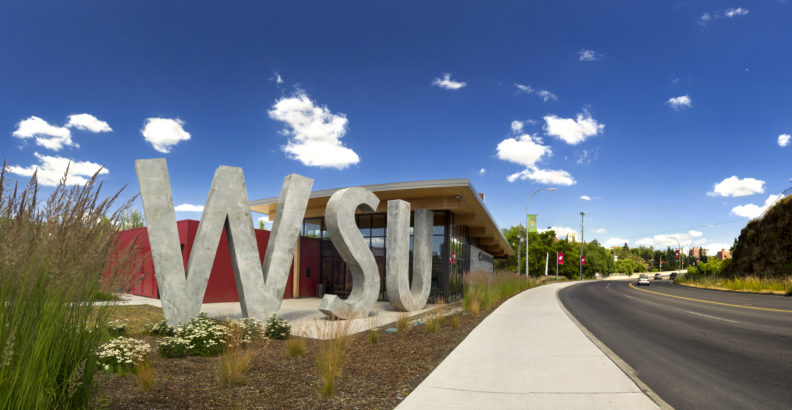 A blue sky with puffy white clouds above the WSU visitor center in Pullman.