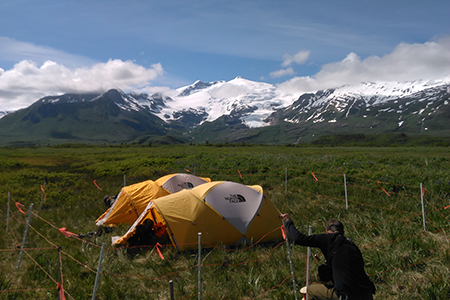 woman setting up electric fence around two tents in a meadow surrounded by mountains