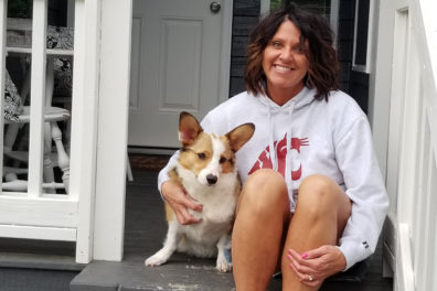 A closeup of Kristy Fiorini and Murray sitting on steps to a porch.