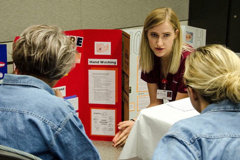 nursing student talking to two women about health issues.