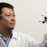 A closeup of Zhang inspecting a molecular model.