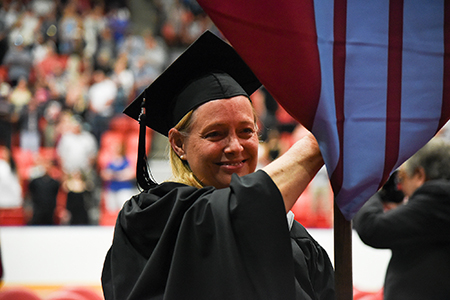 woman in graduation garb carries banner
