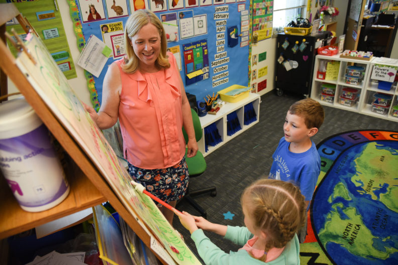 Rausch stands alongside an easel as she works with two kindergarten students.