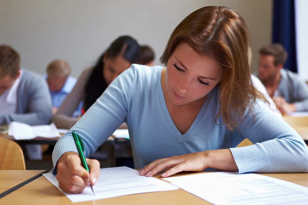 Student at desk filling out paper.