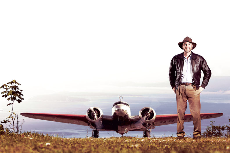 Spink stands in the foreground with WWII era twin-engine plane behind him.