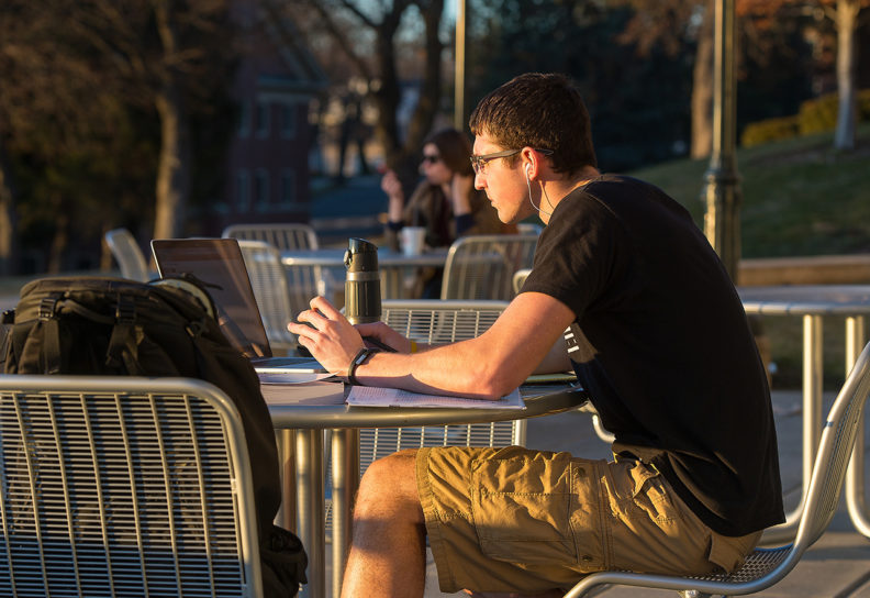 Student in shorts and short sleeve shirt sitting and studying outside.