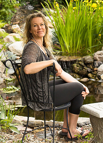 Jennifer Tate sitting in a chair next to a pond.