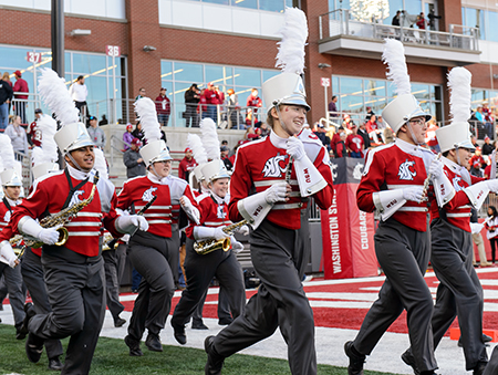 Marching band members run onto the football field.