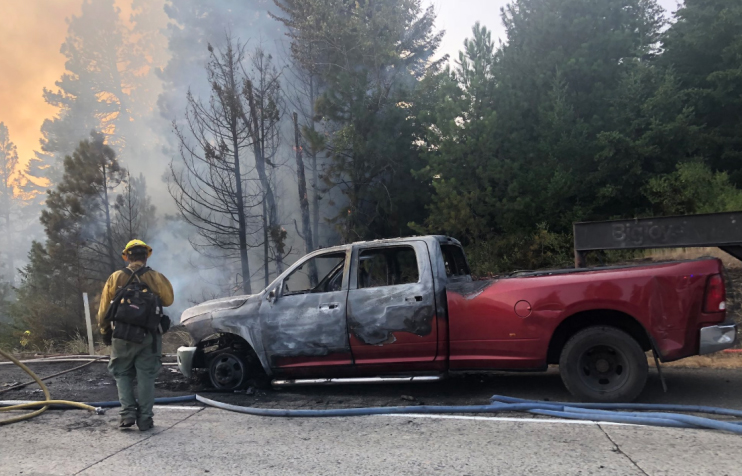 Burned pickup truck with forest blaze in background.