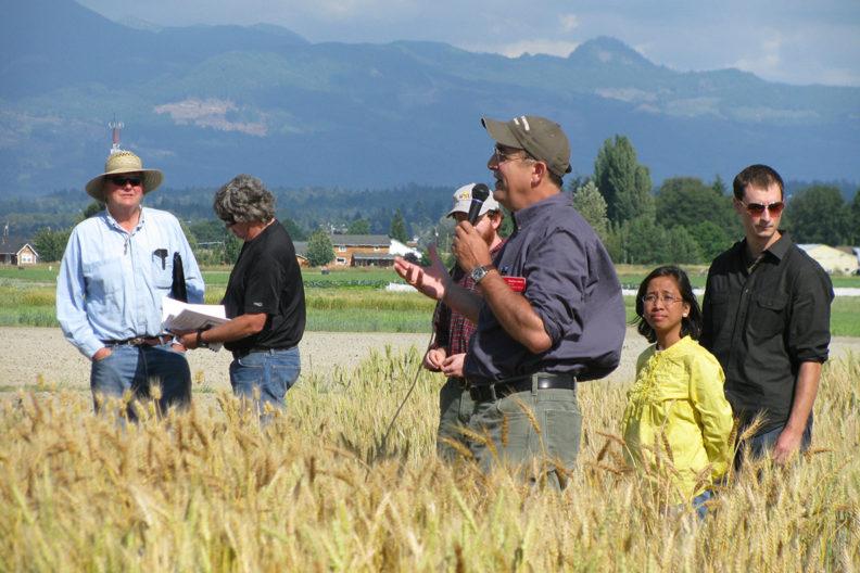 A speaker addresses people in wheat field.