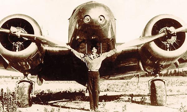Earhart standing in front of plane.