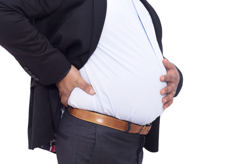 Overweight man with hand on stomach and back.