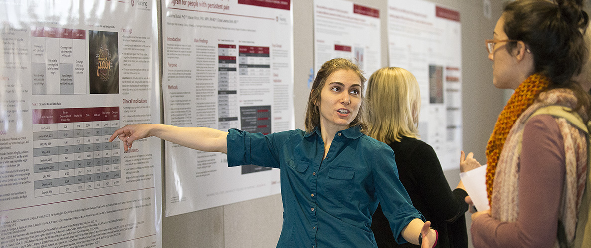 Bigand points at a poster at research symposium.