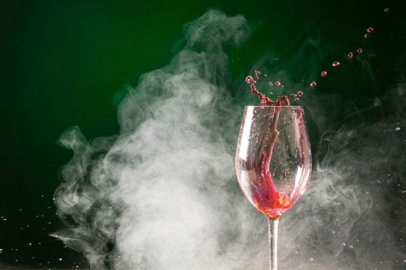 smoke surrounds a glass of wine