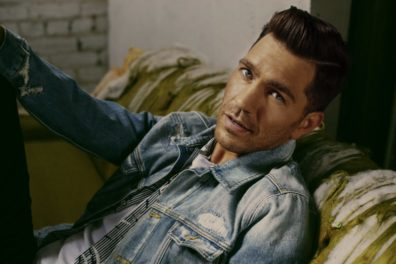 Cloesup of Andy Grammer sitting on couch.