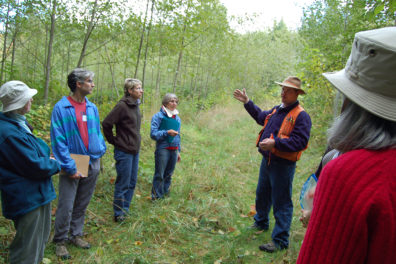 forester talking to group in treed area