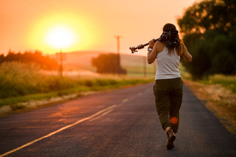 Person walking down road at sunset with camera and tripod over shoulder.