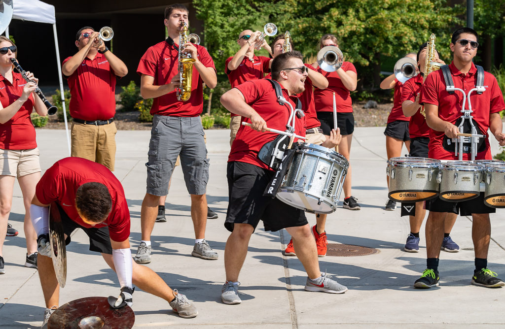Members of the WSU Cougar Marching Band perform in front of a residence hall.