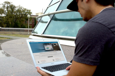 Man using laptop computer outdoors by WSU library.