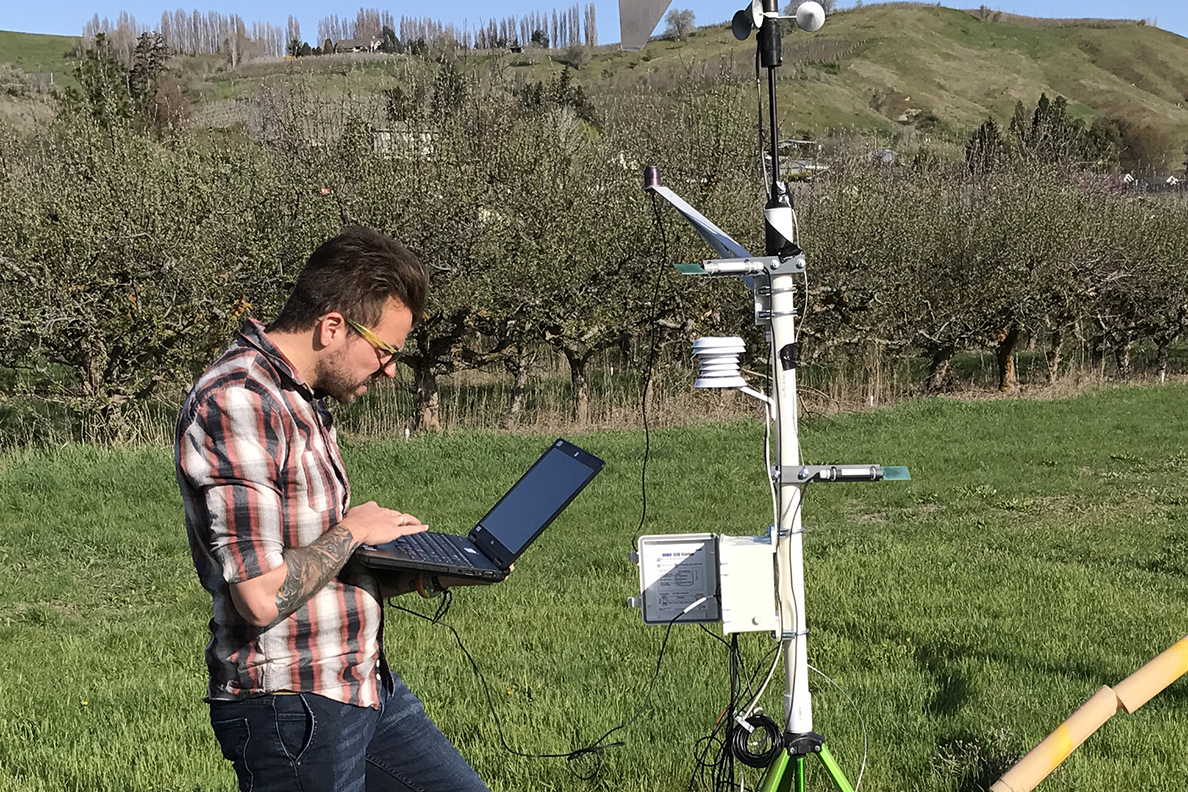 Julián Andrés Valencia Arbeláez uses a laptop to collect information near an apple orchard.
