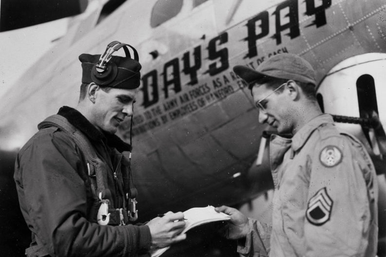 Historic black and white WWII photo with bomber plane and two air force military men.