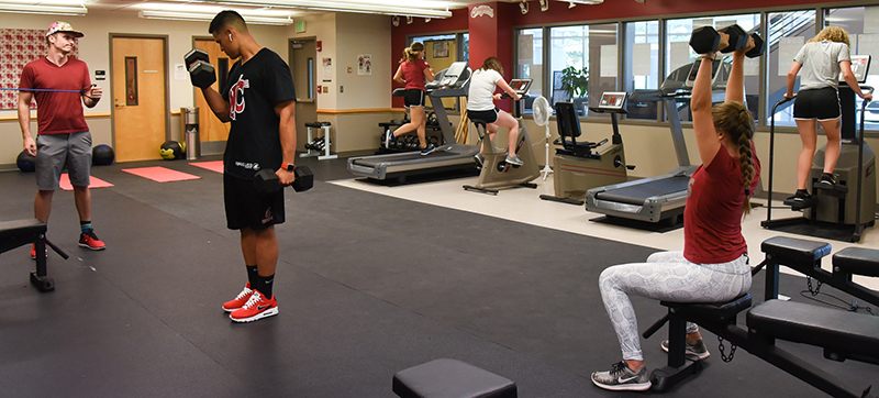 broad view of exercise room with several people exercising