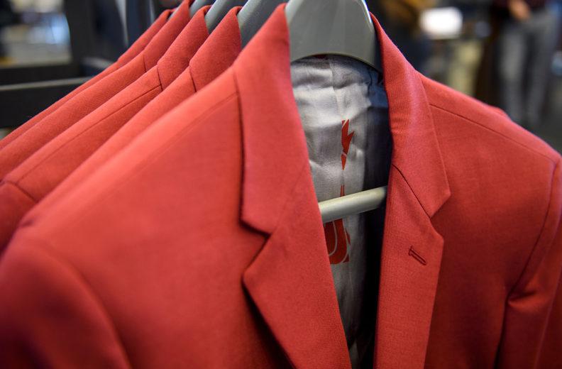 Crimson sport jackets hanging on coat rack.
