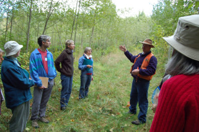 Group of people talking in stand of alder trees.