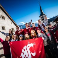 Group of business students holding WSU flag.