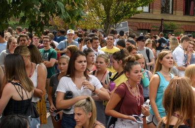 Hundreds of students standing shoulder to shoulder outside.