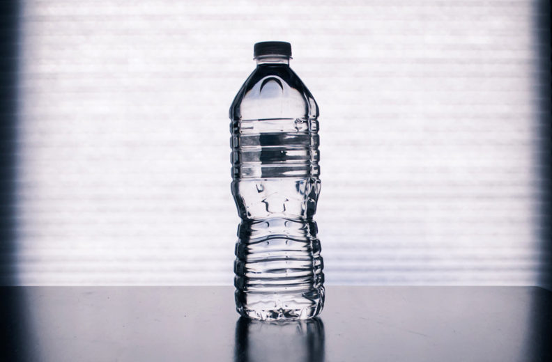 Plastic bottle of water on countertop.
