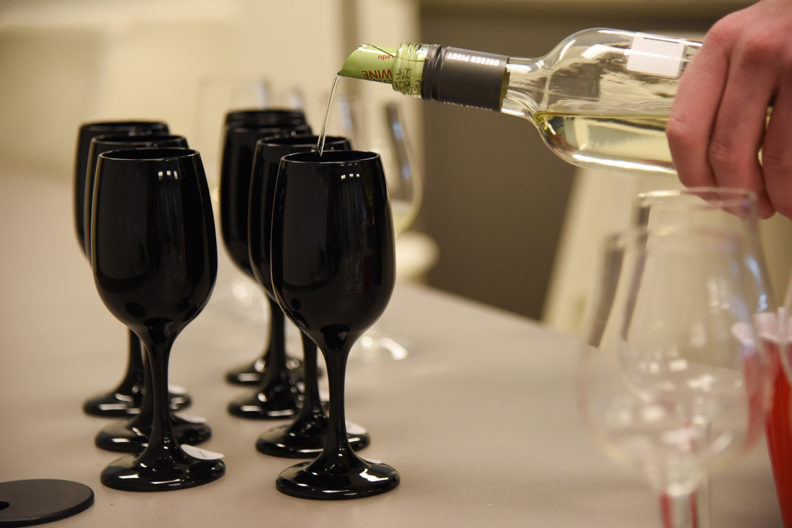 Wine is poured into one of several glasses lined up on a table.