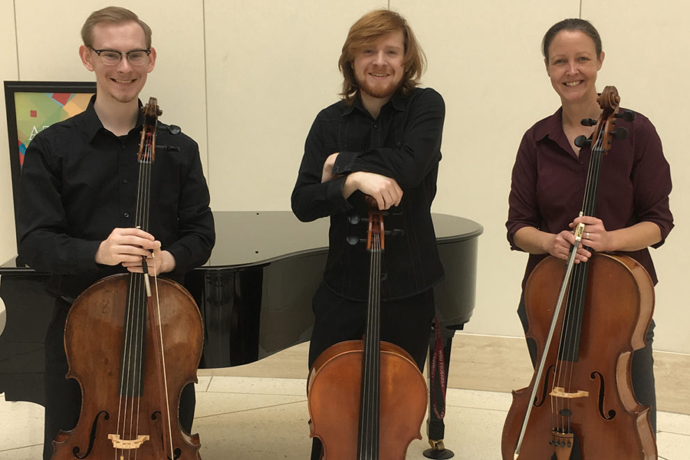 two male students and a female faculty member pose with their cellos.