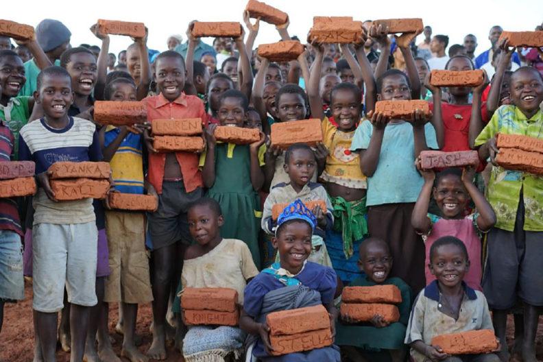 Large group of Malawi children holding bricks.