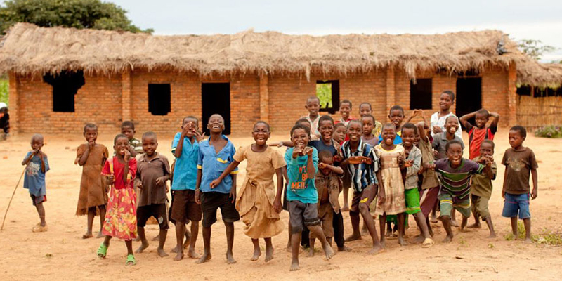 Malawi children in front of thatched roof building.
