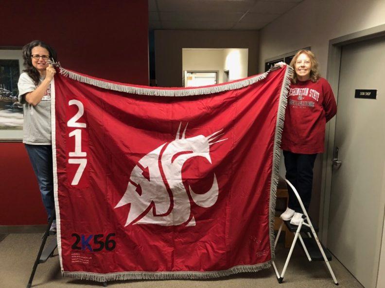 Sharon Macy and Catherine Jasmer hold the Ol' Crimson flag.
