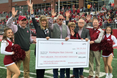 A large, ceremonial check is presented to WSU during a Cougar football game.