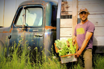 Olson holding a box of produce in front of an antique farm truck.