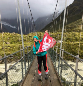 Emma in hiking and winter gear displays wsu flag on a pedestrian bridge over a stream, with snowy mountains towering behind.