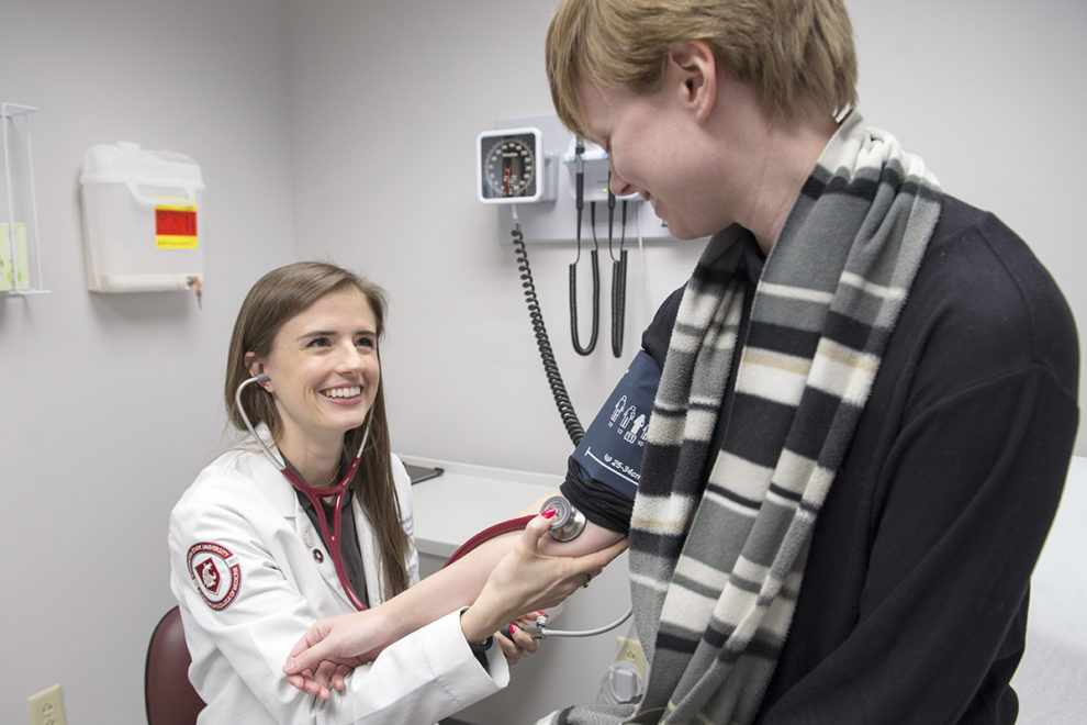 Medical student takes patient's blood pressure.