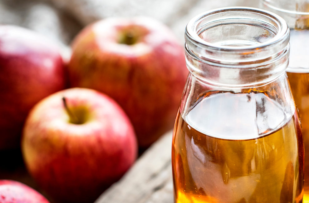 Apples and glass containers of cider.